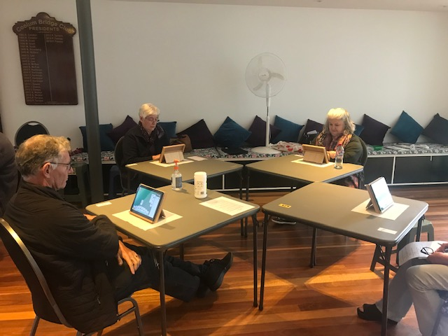Group fo four men and women playing bridge on tablet