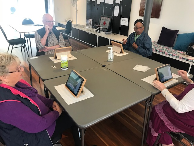 Group of man and woman playing bridge on tablet